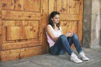 Música de audiência jovem com telefones de orelha, apoiando-se na porta de madeira — Fotografia de Stock