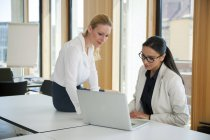 Two businesswomen in office working together on laptop — Stock Photo