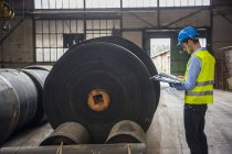 Працівник з документів у залі заводу з рулонів гумові — стокове фото