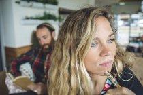 Портрет задумчивой блондинки с ручкой, сидящей в кафе, пока мужчина читает книгу на заднем плане — стоковое фото