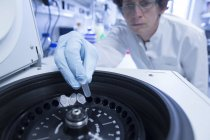Женщина-биолог кладет трубы в центрифугу — стоковое фото