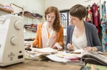 Two female fashion designers at her work desk — Stock Photo