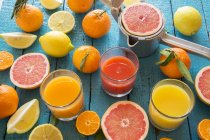 Glasses of orange, grapefruit juice and multivitamin juice with squeezer and fruits on wood — Stock Photo