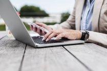 Las manos de la mujer de negocios que teclea en el teclado del portátil al aire libre - foto de stock