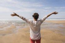 Зрелая женщина, стоящая на пляже в VR очках — стоковое фото