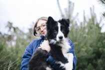 Femme tenant Border Collie à l'extérieur — Photo de stock