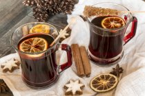 Glasses of mulled wine, orange slices and cinnamon stars on cloth and wooden tray — Stock Photo