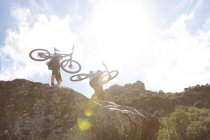 Man and woman carrying mountain bikes on rocks in nature — Stock Photo