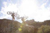 Homme et femme transportant des vélos de montagne sur les rochers dans la nature — Photo de stock