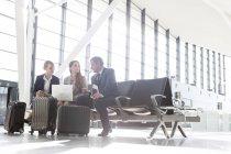 Homme d'affaires et deux femmes d'affaires avec ordinateur portable et bagages à l'aéroport — Photo de stock