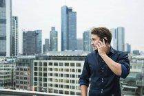 Германия, Гессен, Франкфурт, молодой человек, Телефонировать с его смартфон перед skyline — стоковое фото