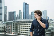 Germany, Hesse, Frankfurt, young man telephoning with his smartphone in front of the skyline — Stock Photo