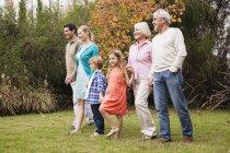 Großfamilie geht Hand in Hand im Garten — Stockfoto