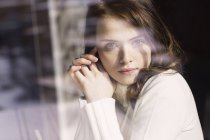 Portrait of young woman looking through window pane of a cafe — Stock Photo