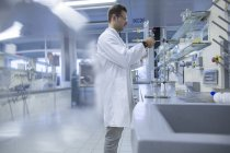 Chimiste travaillant en laboratoire et insérant une burette en verre — Photo de stock