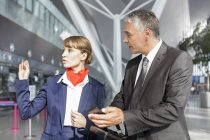 Flight attendant assisting passenger at the airport — Stock Photo