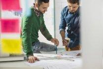 Два молодых человека в офисе обсуждают план строительства — стоковое фото