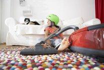 Мальчик в гостиной с кошкой и пылесосом — стоковое фото