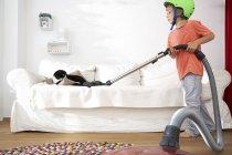Мальчик в гостиной пылесосит диван с котом — стоковое фото