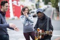 Junges paar anhören Gitarrist auf der Straße — Stockfoto