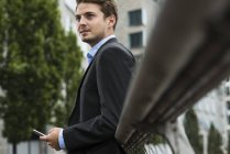 Portrait of  young businessman with smartphone standing on a bridge — Stock Photo