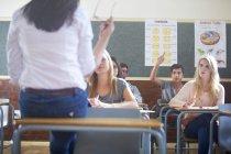 Estudante do sexo masculino em sala de aula levantando mão — Fotografia de Stock