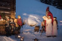 Famille heureuse avec les anges et le père Noël à la cabane en bois dans la neige — Photo de stock