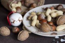 Plat de différentes noix et décoration de Noël — Photo de stock