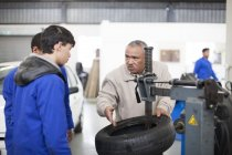 Instructor teaching trainees in repair garage — Stock Photo