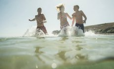 Three laughing teenagers running in sea — Stock Photo