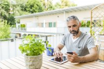 Portrait of man sitting on his balcony using  smartphone and digital tablet — Stock Photo