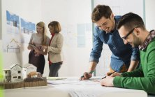 Young architects in office looking at construction plan — Stock Photo