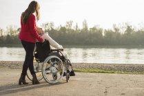 Дорослий внучки, допомагаючи бабуся, сидячи в інвалідному візку — стокове фото