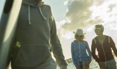 Three teenagers walking on the beach at evening twilight — Stock Photo