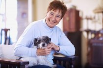 Happy senior woman with dog at home — Stock Photo