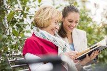 Внучка с бабушкой смотрят фотоальбом — стоковое фото