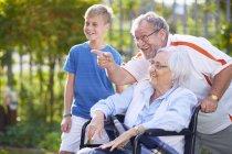 Указывая дед и внук с бабушкой в инвалидной коляске — стоковое фото