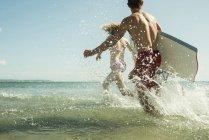 Adolescents des planches de surf à bord de l'eau de la mer — Photo de stock