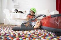 Вымотанный мальчик в гостиной с кошкой и пылесосом — стоковое фото