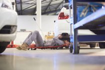 Car mechanic on creeper dolly at work in repair garage — Stock Photo