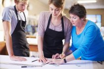 Three people in a workshop manufacturing stained glass — Stock Photo