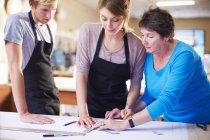 Drei Menschen in einer Werkstatt, die Herstellung von Glasmalereien — Stockfoto
