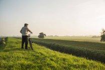 Старший чоловік у сільських ландшафтів, штовхаючи велосипеда — стокове фото