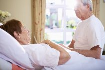 Senior woman lying in hospital bed talking to senior man — Stock Photo