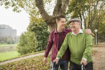 Senior man and adult grandson walking in park — Stock Photo
