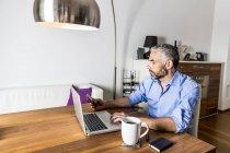 Retrato de hombre de negocios trabajando con el portátil en casa oficina - foto de stock