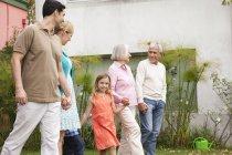 Расширенная семья ходьбе рука в руку в саду — стоковое фото