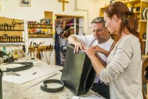 Saddlers manufacturing leather rucksack in workshop — Stock Photo