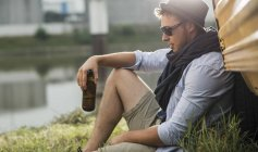 Young man leaning against vehicle holding bottle of beer — Stock Photo