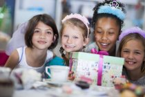 Girls with gift on a birthday party — Stock Photo